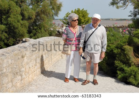 Happy senior couple walking along the coast of Brittany - stock photo