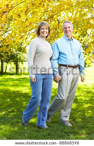 Happy senior couple walking at the park. - stock photo