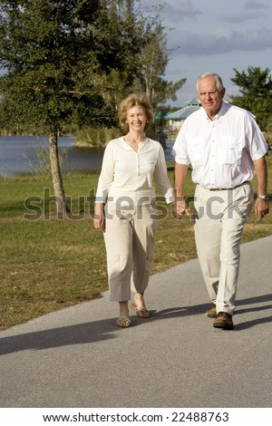 Happy senior couple walking in a park - stock photo