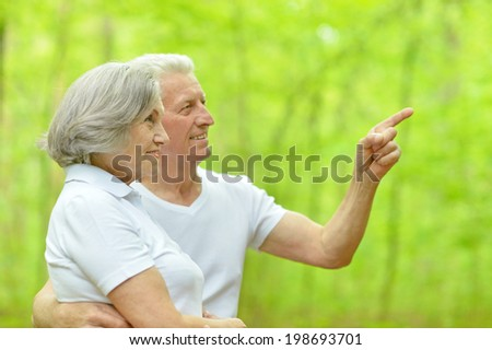 happy senior couple walking in summer forest