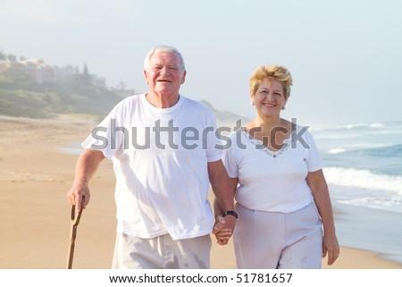 happy senior couple walking on beach - stock photo