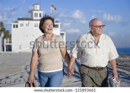 Happy senior couple walking together in leisure time on beach - stock photo