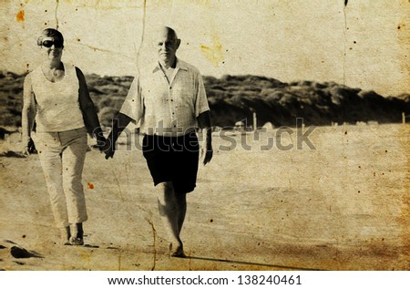 Happy senior couple walking together on a beach. Photo in old image style. - stock photo