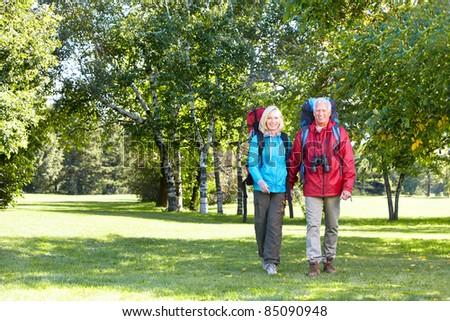 Happy senior couple walking with backpacks. Adventure. - stock photo