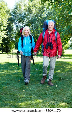 Happy senior couple walking with backpacks. Adventure. - stock photo