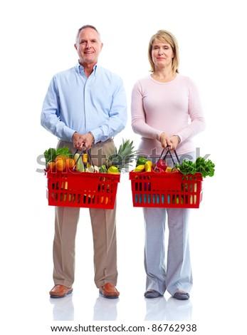 Happy senior couple with a shopping basket . Isolated over white background. - stock photo