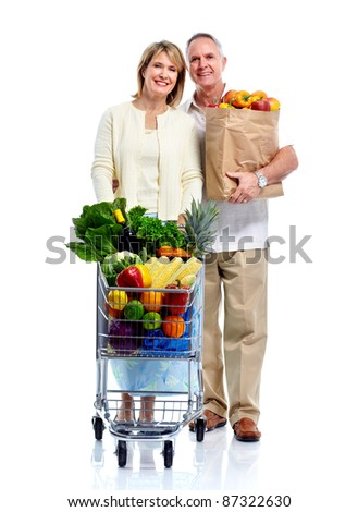 Happy senior couple with a shopping cart. Isolated over white background.