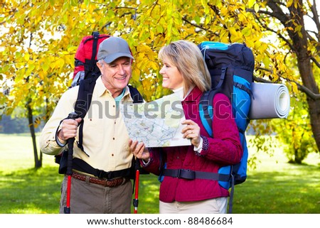 Happy senior couple with backpacks and trekking poles. - stock photo