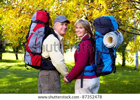 Happy senior couple with backpacks in the park. - stock photo