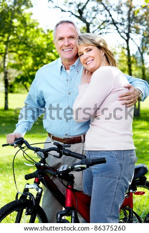 Happy senior couple with bicycle in the park.