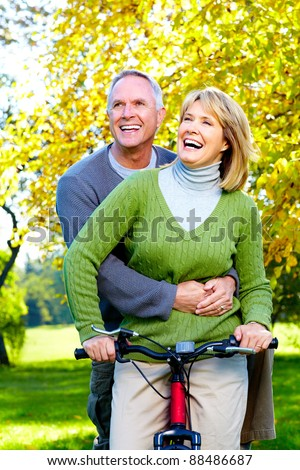 Happy senior couple with bicycle in the park. - stock photo