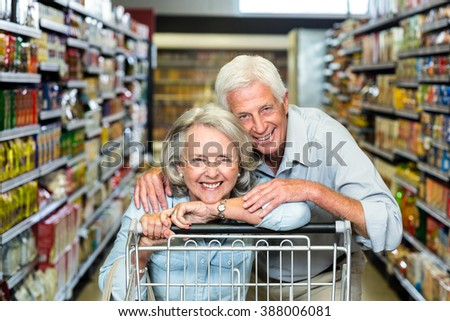 Happy senior couple with cart smiling at the camera
