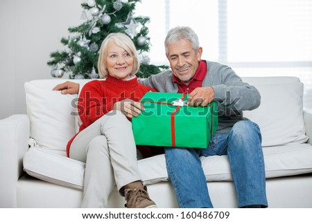 Happy senior couple with Christmas gift sitting on sofa at home