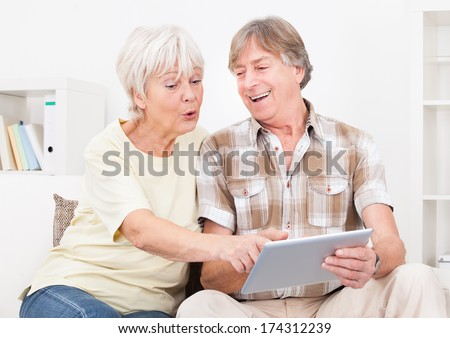 Happy Senior Couple With Digital Tablet Surfing On The Internet At Home - stock photo