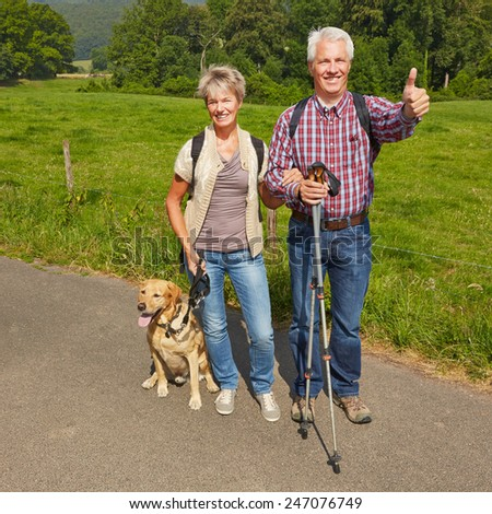 Happy senior couple with dog in nature holding thumbs up - stock photo