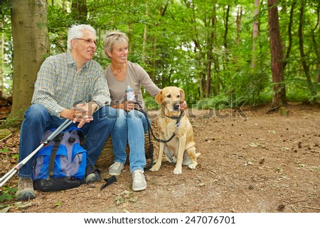 Happy senior couple with dog taking a break in a forest - stock photo