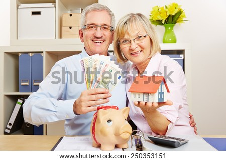 Happy senior couple with Euro money bills and house and piggy bank - stock photo