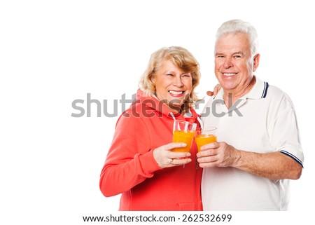 Happy Senior Couple with Glasses of Orange Juice Isolated on a White Background. - stock photo