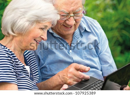 Happy senior couple with  laptop, outdoors - stock photo