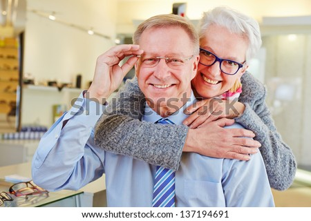 Happy senior couple with new glasses at optician retail store - stock photo
