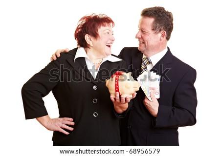 Happy senior couple with piggy bank and Euro money - stock photo