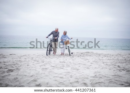 Happy senior couple with their bike on the beach - stock photo