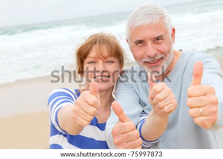 Happy senior couple with thumbs up at the beach - stock photo