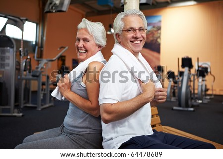 Happy senior couple with towels in a gym