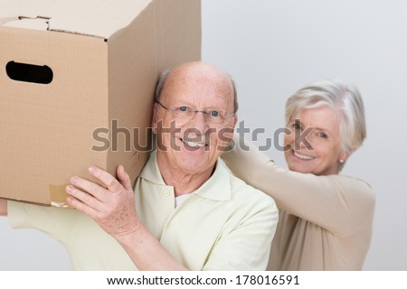 Happy senior couple working as a team as they move house assisting each other to carry a large brown cardboard box - stock photo