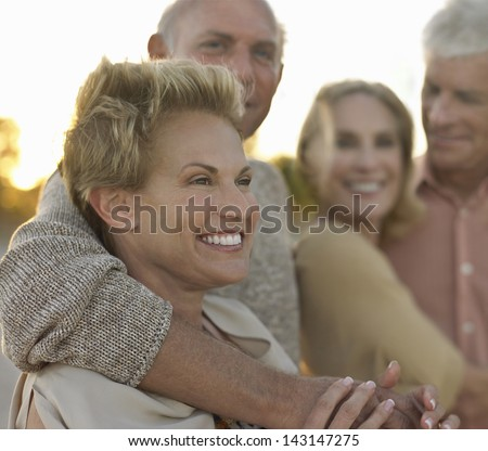 Happy senior couples spending time together on tropical beach - stock photo