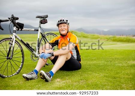 happy senior cyclist sitting on grass resting - stock photo