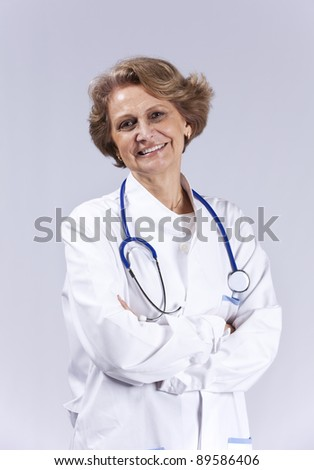 Happy senior doctor smiling (isolated on gray) - stock photo