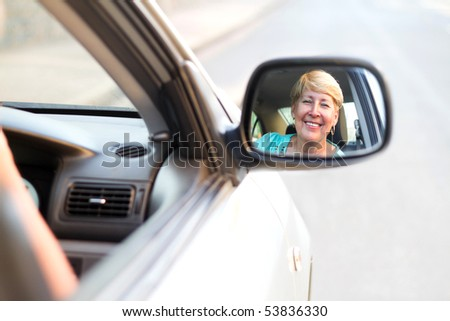 happy senior driver looking at side mirror - stock photo