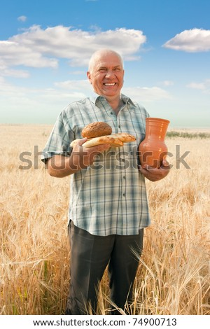 Happy senior farmer with differents  baking foods and  jug - stock photo
