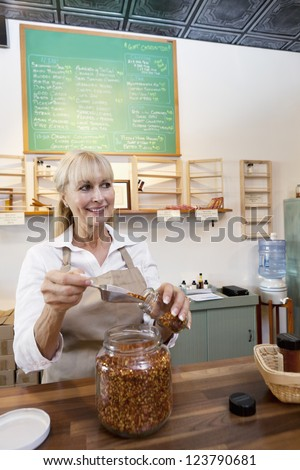 Happy senior female filling jar with scoop while looking away in store