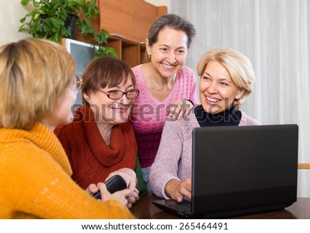 Happy senior female friends working with notebook using wifi - stock photo
