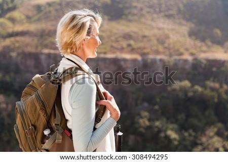 happy senior female hiker enjoying outdoor activity - stock photo