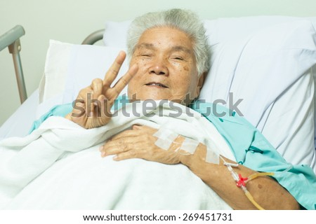 Happy senior female patient making finger victory sign for cheerful in bed at hospital - stock photo