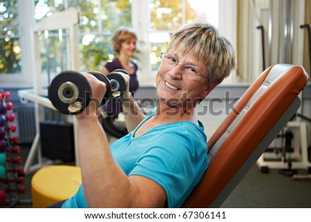 Happy senior female with dumbbells in gym - stock photo