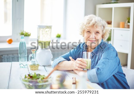 Happy senior female with glass of fruit smoothie looking at camera - stock photo