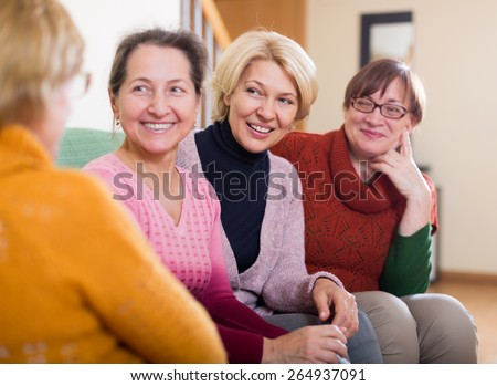 Happy senior friends chatting in living room at home - stock photo