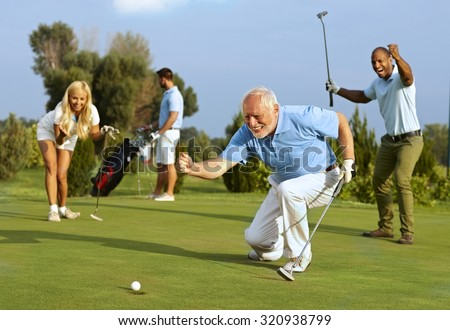 Happy senior golfer following golf ball to hole after putting. - stock photo
