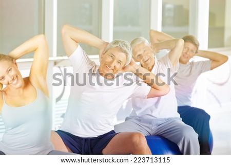 Happy senior group doing back training in gym on exercise balls - stock photo