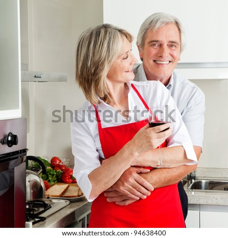 Happy senior husband embracing smiling wife in kitchen
