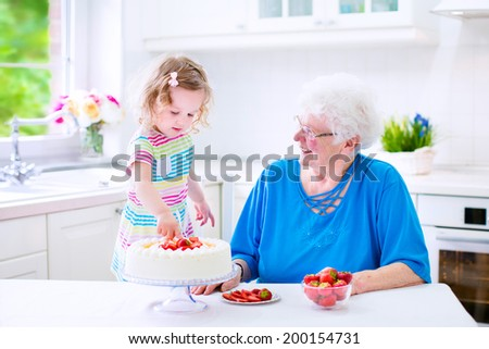 Happy senior lady, loving grandmother, baking a homemade strawberry cake with her granddaughter, adorable curly toddler girl in a colorful summer dress, in a white modern kitchen with window - stock photo