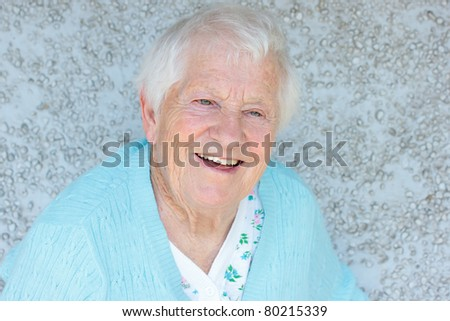 Happy senior lady smiling in front of light blue stone wall - stock photo
