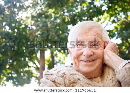 Happy senior lady smiling outside - stock photo