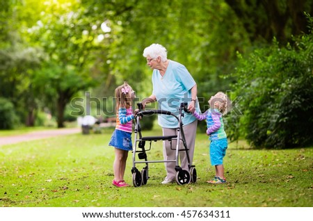 Happy senior lady with a walker holding hands of little boy and girl. Grandmother with grand children enjoy a walk in summer park. Kids supporting disabled grandparent. - stock photo