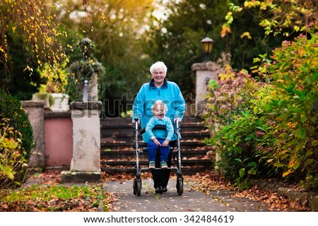 Happy senior lady with a walker or wheel chair and children. Grandmother and kids enjoying a walk in the park. Child supporting disabled grandparent. Family visit. Generations love and relationship. - stock photo
