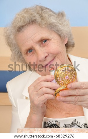 happy senior lady with lipstick and mirror - stock photo